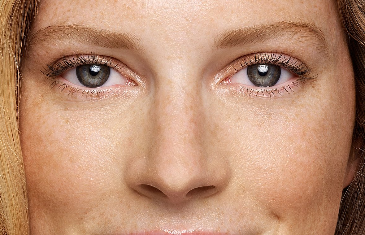 a woman with blue eyes and ACUVUE Define Natural Shimmer looking straight into the camera