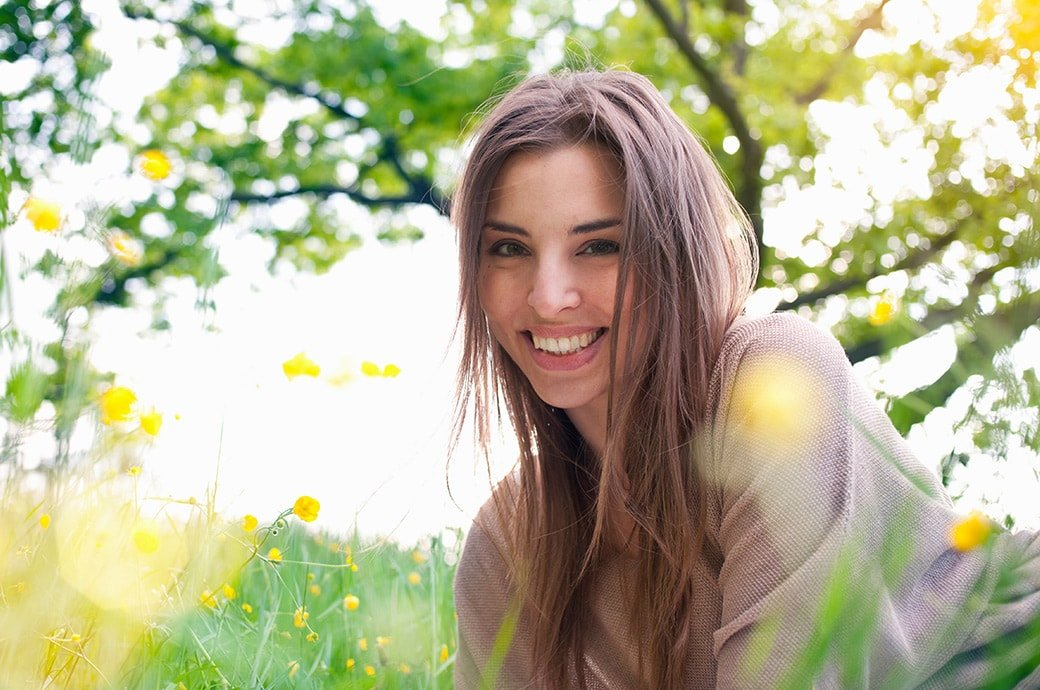 Adult woman smiling as she lays on the grass with the sun shining.
