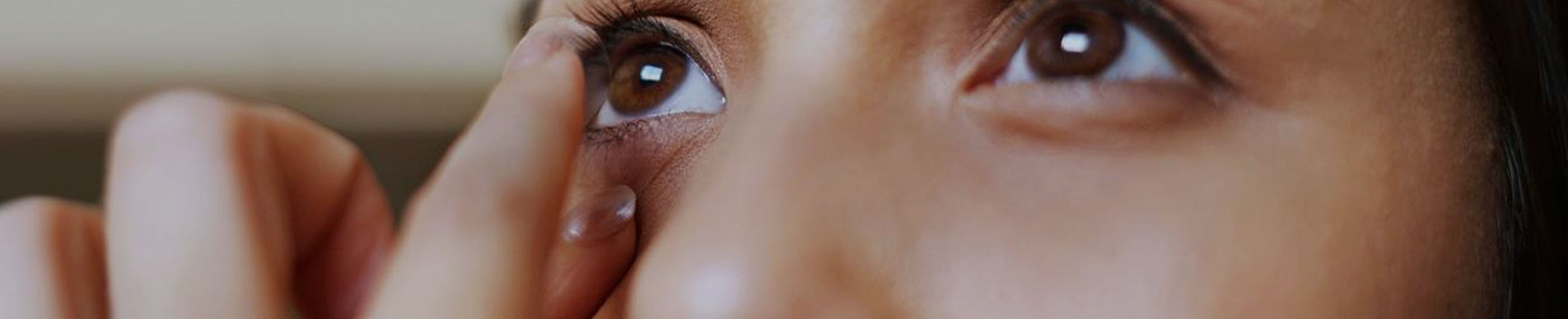 A close-up of a young woman looking into a mirror putting her contact lenses on.