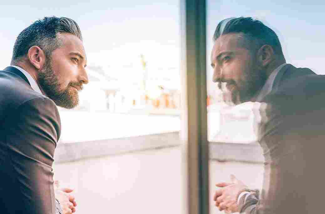 Image of a mature man looking at his reflection in a window