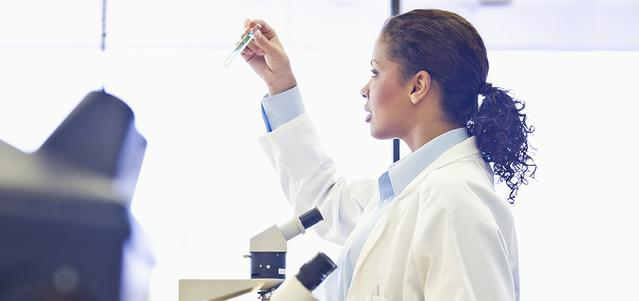 A doctor in a lab coat inspecting a test tube