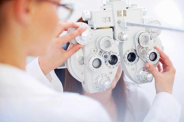 A young woman behind a phoropter as the optician checks her eyes during an eye exam.