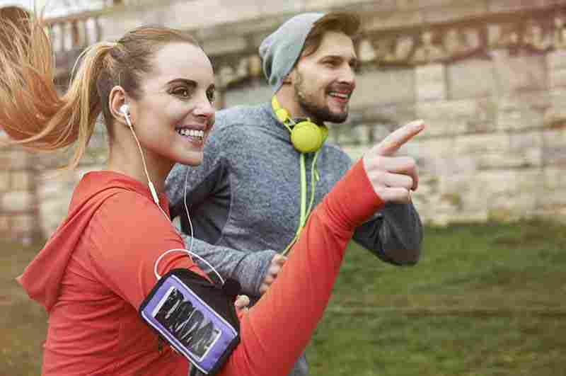 A woman and man on a run outdoors.