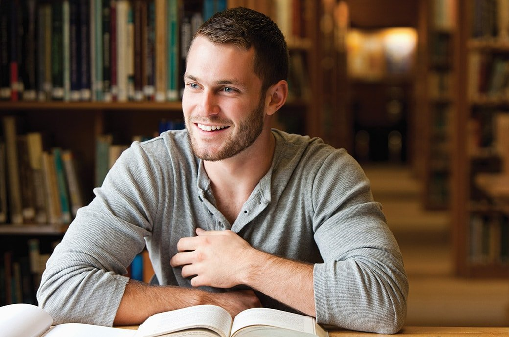 A man at the library smiling with books on the table.
